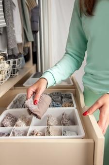 Неизвестная аккуратная хозяйка складывает контейнер с носками, трусиками и нижним бельем. хранение одежды.