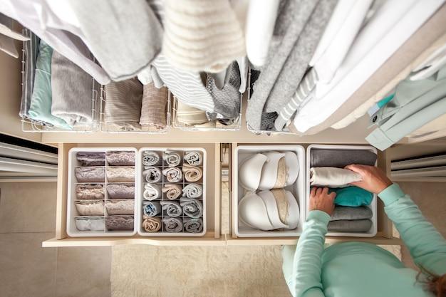正体不明の清楚な主婦が靴下、パンティー、下着の入った容器を置きます。洋服収納。