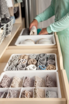 Unidentified neat housewife puts container with socks, panties and underwear. clothes storage.