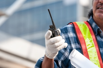 Unidentified senior Asian civil engineer wearing glove holding walkie talkie
