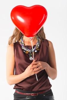 풍선과 함께 사무실 옷을 입고 포즈를 취하는 정체 불명의 날씬한 젊은 여자