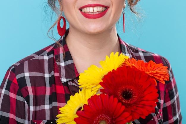 파란색 벽에 포즈를 취하는 그녀의 손에 밝은 gerbera 꽃의 꽃다발을 들고 격자 무늬 셔츠에 미확인 된 웃는 아름 다운 젊은 여자. 휴일 및 선물의 개념입니다.