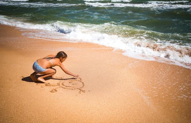 정체 불명의 검게 그을린 어린 소녀는 화창한 따뜻한 여름 날에 폭풍우 치는 바다 파도 근처의 모래에 그립니다.