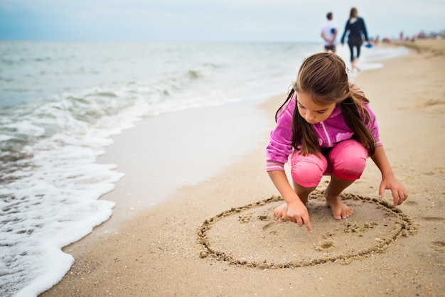Unidentified tanned little girl draws a smile