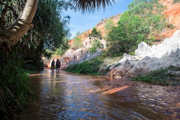 ベトナム、ムイネーの岩とジャングルの間のフェアリーストリームレッド川での正体不明の観光客