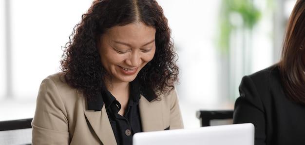 正体不明の認識できないアジアの中年女性の女性実業家がフォーマルなスーツを着て、レポートの書類がいっぱいのテーブルに並んでタイピングノートパソコンを入力しています。