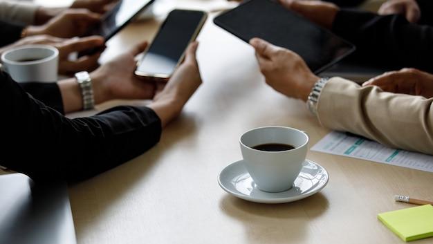 正体不明の認識できないビジネスマンが、会議室の会社のオフィスの作業テーブルの周りに、コピースペースのテキストが付いた黒い空白のデジタルタッチスクリーンタブレットとスマートフォンのガジェットを一緒に見せています。