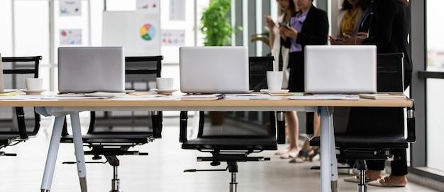 正体不明の認識できない女性警官のスタッフが、ラップトップノートブックコンピューターの事務処理でオフィスのワークスペースでスマートフォンを使用して休憩を取りながら立ってチャットし、作業テーブルのコーヒーカップを記録します。
