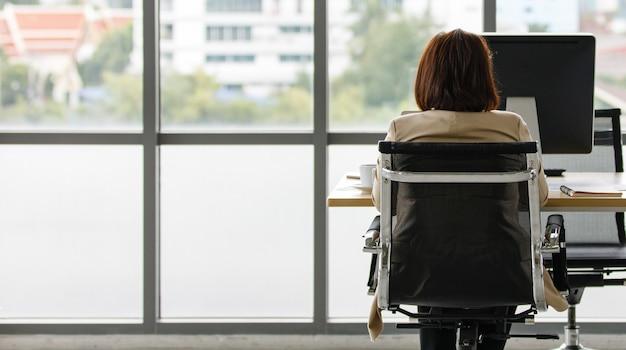 会社の建物の高いガラス窓の前で一人でオフィスのテーブルでタイピングをしている椅子に座っている正式なビジネススーツの正体不明の認識できない女性の成功した女性秘書。