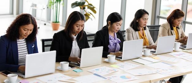 会社のオフィスのラップトップノートブックコンピューターで情報を入力する作業机に並んで座っているカジュアルなスーツを着た正体不明の認識できない女性の成功した実業家秘書オペレーター。