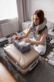 Неизвестная женщина, упаковывающая нижнее белье в ящик для хранения, использует метод конмари, готовясь к отпуску