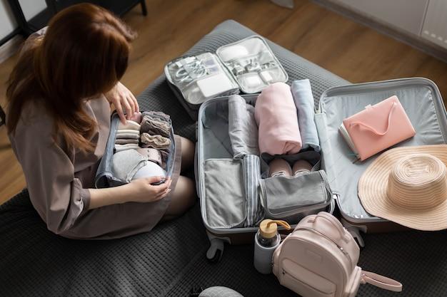 Неизвестная женщина кладет нижнее белье в дорожный контейнер для хранения, используя чемодан для упаковки по методу конмари
