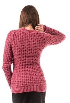 赤いセーターとベージュのズボンでスタイリッシュな婦人服でポーズをとる正体不明の若いブルネットの女性