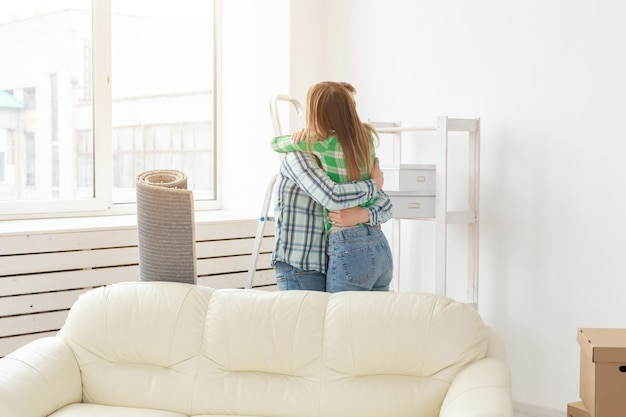 Неизвестная молодая пара обнимается и танцует в гостиной своей новой квартиры. концепция