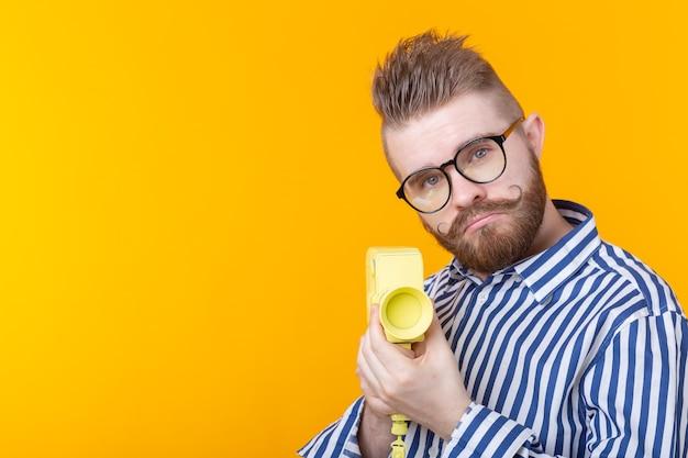 黄色の壁に口ひげとあごひげを生やした黄色のカメラを持つ正体不明の若い男