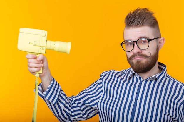 콧수염과 수염을 가진 노란색 카메라로 정체 불명의 젊은 남자