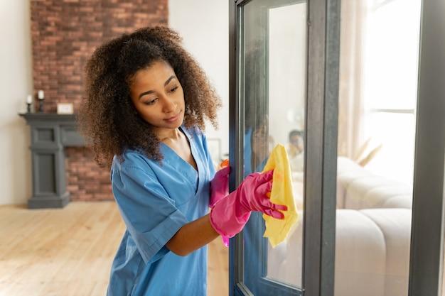 ユニフォームと手袋。ガラスのドアを掃除する制服と手袋を着用した若い浅黒い肌の医療従事者