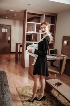 Униформа и каблуки. светловолосая домработница в униформе и на высоких каблуках выходит из комнаты