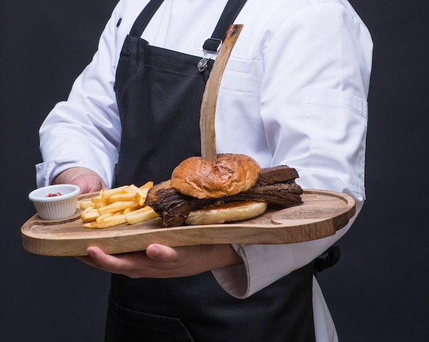A uniformed chef serves a meat dish on a wooden tray