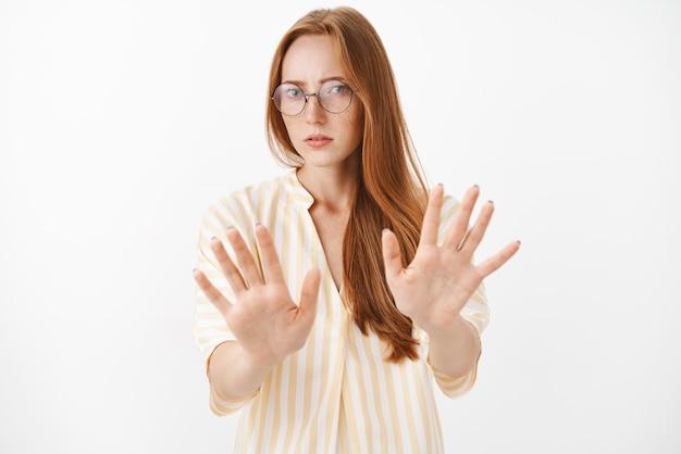 Не впечатленная и недовольная властная женщина-журналистка в модных очках с веснушками, тянущая ладони к себе в знак отказа или прекращения жестов, которым не нравится, предлагает смотреть с отвращением