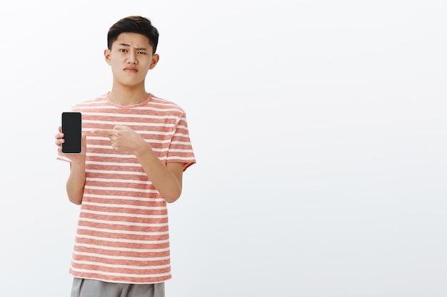실망스럽고 무관심한 아시아 스마트 남성 학생이 스마트 폰을 들고 의심의 여지가있는 한쪽 눈썹을 올리는 장치 화면을 가리키며 입술을 움켜 쥐고
