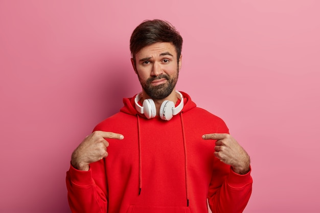 Unimpressed unshaven caucasian guy points at himself, asks who me, has calm face expression, wears red sweatshirt, listens audio via headset, shows new bought outfit, poses over pink wall