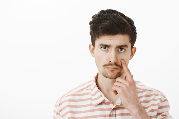 Unimpressed with boring conversation. displeased bored guy in casual striped shirt, pulling eye and showing eyelid with indifferent careless expression, standing gloomy and calm over gray wall