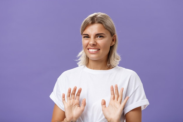 Unimpressed woman unwilling accept offer raising palms in no rejection gesture clenching teeth while smiling with intense displeased