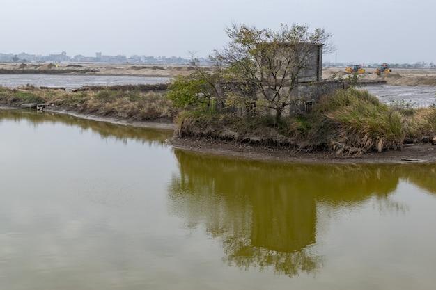 Нежилые дома на песке отражаются в воде