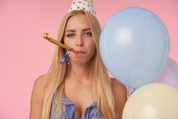 영감을받지 않은 젊은 긴 머리 금발 여성, 여러 가지 빛깔의 헬륨 풍선과 함께 실내 포즈, 파티 경적을 불고 분홍색 배경 위에 서있는 지루한 얼굴로 카메라를보고