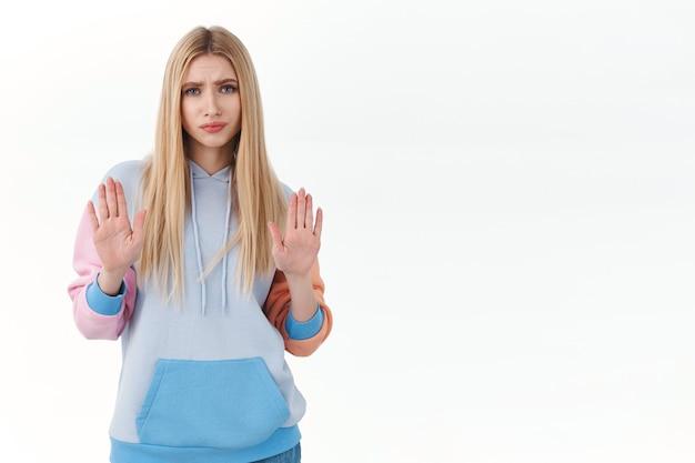 Незаинтересованная, скептически настроенная белокурая девочка-подросток, показывающая знак остановки, поднимающая руки в отказе