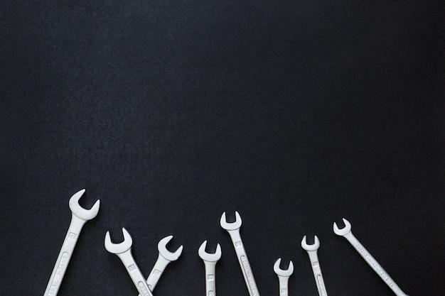 ユニオン、スパナ、ネジ、黒の背景にさまざまなレンチツール、上からの眺め