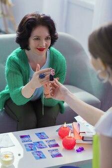 Уникальный амулет. симпатичная темноволосая женщина улыбается, показывая особый камень своему клиенту