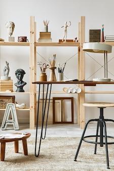 スタイリッシュなデスク、木製のイーゼル、本棚、アートワーク、絵画アクセサリー、装飾、エレガントな個人的なものを備えたユニークなアーティストワークスペースのインテリア。アーティストのためのモダンなワークルーム。レンプレート。