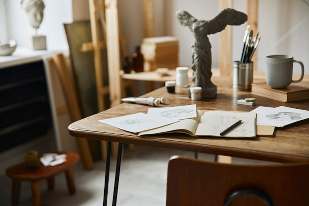 Unique artist workspace interior with stylish desk, wooden easel, bookcase, artworks, painting accessories, decoration and elegant personal stuff. modern work room for artist. template.