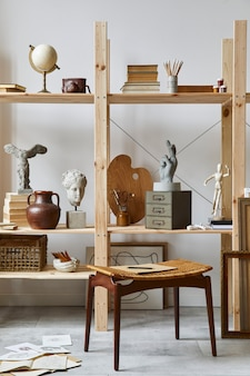 세련된 의자, 나무 책장, 예술품, 그림 액세서리, 장식 및 우아한 개인 용품을 갖춘 독특한 예술가 작업 공간 인테리어. 예술가를위한 현대적인 작업실 ..