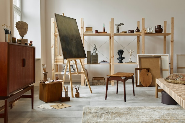 スタイリッシュなチーク材の箪笥、木製のイーゼル、本棚、アートワーク、絵画のアクセサリー、装飾、エレガントな個人的なものを備えたユニークなアーティストワークスペースのインテリア。アーティストのためのモダンなワークルーム。レンプレート。