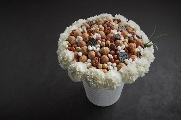 Unique bouquet made up of different types of nuts, decorated with flowers