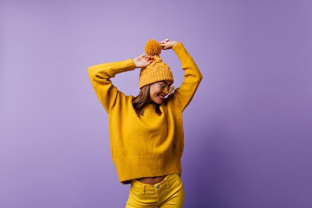 紫に恥ずかしそうにポーズをとるユニークで魅力的な女の子。スタイリッシュな服装でヨーロッパからのモデルの肖像画