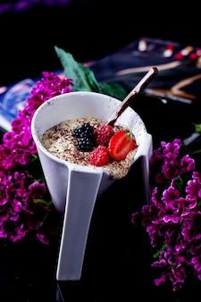 Una tazza unica di budino alla vaniglia con granelli di caffè e bacche