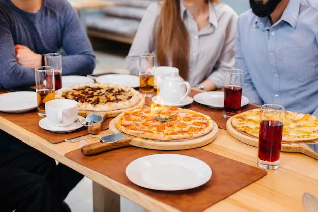 Уникальная горячая пицца на огне крупным планом во время дружеского ужина