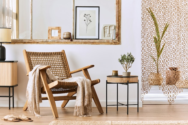 Unique living room interior with stylish rattan armchair,  design furniture, dried flowers, poster frame,  wooden floor, decoration and elegant personal accessories