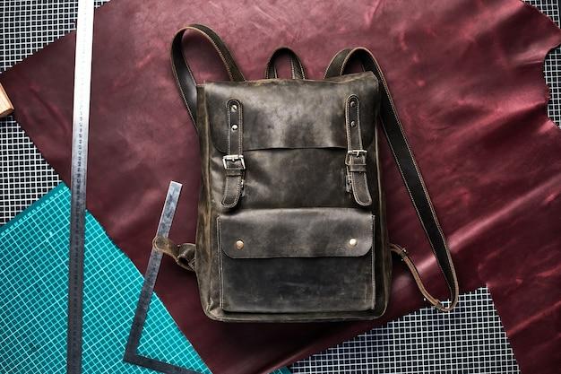 Унисекс коричневый кожаный рюкзак на фоне поделок в мастерской на столе, кожаный рюкзак ручной работы.
