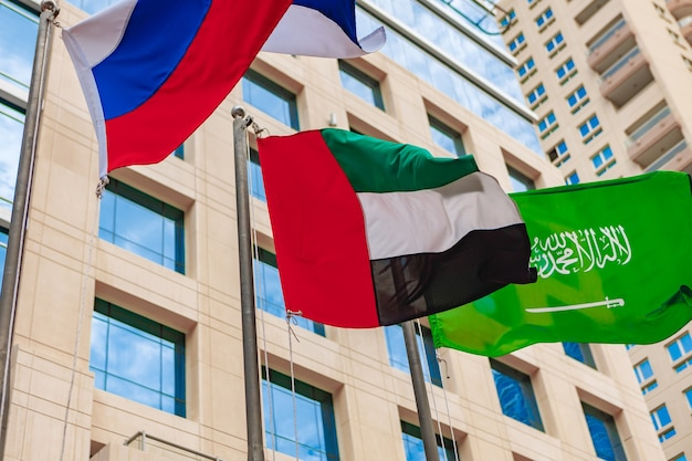 United arab emirates and russia flag waving against building