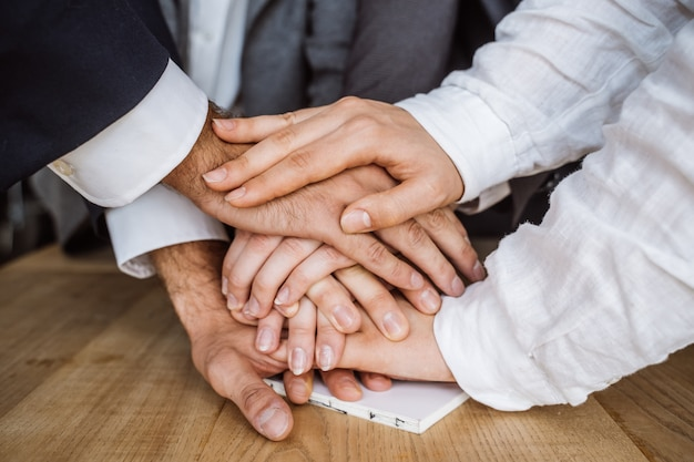 Объединенные руки бизнес-команды на фоне рабочей области