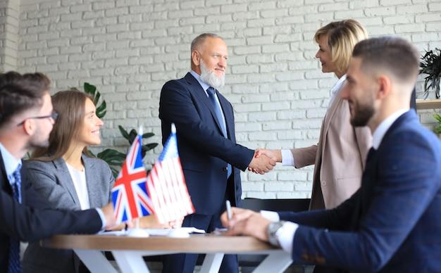 거래 계약에 악수 하는 영국과 미국 지도자.