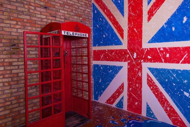 イギリスの旗と赤い電話ブース、デザインと創造性のためのヴィンテージの壁のテクスチャの背景。