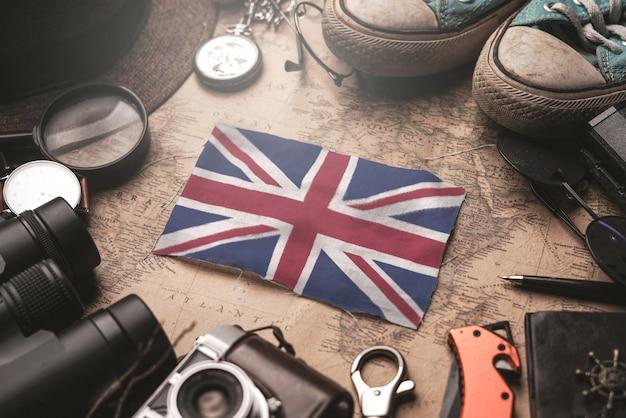 Флаг великобритании между аксессуарами путешественника на старой винтажной карте. концепция туристического направления.