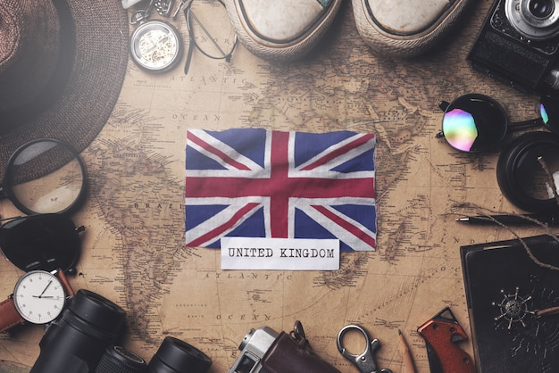 United kingdom flag between traveler's accessories on old vintage map. overhead shot