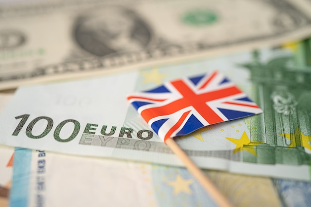 United kingdom flag with us dollar and euro banknotes; banking account, investment analytic research data economy, trading, business company concept.